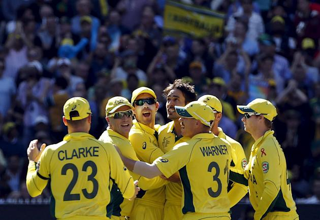 Australia's Mitchell Johnson celebrates with team mates after catching out New Zealand's Kane Williamson for twelve runs during their Cricket World Cup final match at the MCG