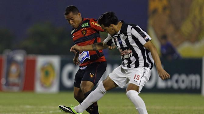 Marcos Aurelio, of Brazil's Sport Recife, left, fights for the ball with Gustavo Gomez, of Paraguay's Libertad, at a Copa Sudamericana soccer game in Asuncion, Paraguay, Wednesday, Sept. 25, 2013