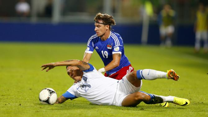 Liechtenstein's Christen challenges Cholevas of Greece during their 2014 World Cup qualifying match in Vaduz
