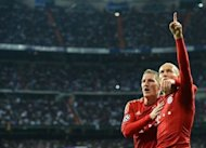 Bayern Munich's Dutch midfielder Arjen Robben (R) celebrates with Bayern Munich's midfielder Bastian Schweinsteiger after scoring from the penalty spot during the UEFA Champions League second leg semi-final football match Real Madrid against Bayern Munich at the Santiago Bernabeu stadium in Madrid. Bayern advanced to the final on penalties