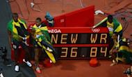 Jamaica's Usain Bolt, Nesta Carter, Yohan Blake and Michael Frater pose for pictures near the New World Record sign after they won the gold medal in the men's 4x100m relay final at the athletics event of the London 2012 Olympic Games