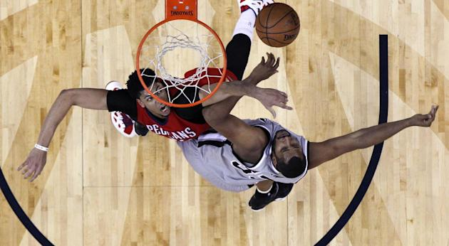 New Orleans Pelicans forward Anthony Davis, top left, and San Antonio Spurs center Boris Diaw (33) battle under the basket in the first half of an NBA basketball game in New Orleans, Wednesday, April
