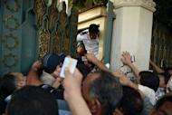 """Egyptian guards try to close the gate of presidential palace to the people wanting to make personal requests to President Mohamed Morsi in Cairo. The ruling military convened an urgent meeting """"to discuss the presidential measures"""" state television says"""