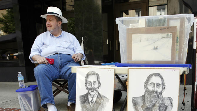 FILE - In a Saturday, June 9, 2012 file photo, regional artist J.D. Hall sells his artwork which includes prints of Randolph McCoy, left, and Devil Anse Hatfield during the Hatfield-McCoy Reunion in Williamson, W.V. Artifacts unearthed last year during filming of a new National Geographic Channel show appear to pinpoint the location of an 1888 ambush on Randolph McCoy's cabin by the Hatfield clan in the woods of eastern Kentucky. Excavators found bullets believed to have been fired by the McCoys in self-defense, along with fragments of windows and ceramic from the family's cabin. Property owner Bob Scott, a Hatfield descendant, plans to capitalize on the historic 70-acre site in eastern Pike County near the West Virginia line. The options include a housing development featuring horseback and ATV trails, he said. (AP Photo/ James Crisp, File)