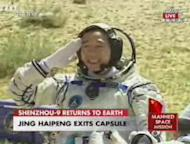 Chinese astronaut Jing Haipeng, commander of the Shenzhou 9 mission, salutes after exiting the space capsule following landing in Inner Mongolia autonomous mission on June 28, 2012.
