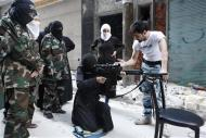 """A female member of the """"Mother Aisha"""" battalion receives instruction as she holds a rifle during military training in Aleppo's Salaheddine district, September 19, 2013. REUTERS/Loubna Mrie"""