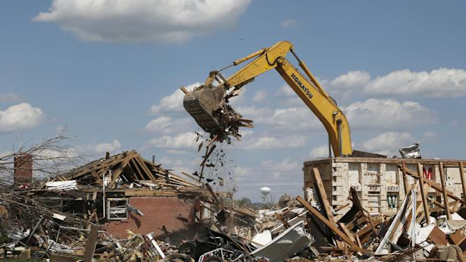 FILE - In this Friday, June 7, 2013 file photo, heavy equipment removes debris from a home destroyed by the May 20, 2013 tornado in the Plaza Towers neighborhood of Moore, Okla. In 2013, in the nation's heartland, tornadoes are flirting with a record for the fewest, with just a bit more than half the normal number of nearly 1,300 twisters reported by mid-September. A shift in the jet stream is credited. (AP Photo/Sue Ogrocki)