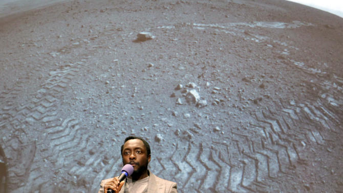 """Will.I.Am, with Black Eyed Peas, sings at Nasa's  Jet Propulsion Laboratory Tuesday Aug. 28, 2012, in Pasadena, Calif. The NASA rover Curiosity beamed to Earth his new song """"Reach for the Stars"""" on Tuesday in the first music broadcast from another planet, to the delight of students who gathered at the Jet Propulsion Laboratory to listen. Earlier, engineers uploaded the song to the rover, which landed near the equator of Mars, and played it back _ a journey of some 700 million miles. (AP Photo/Nick Ut)"""