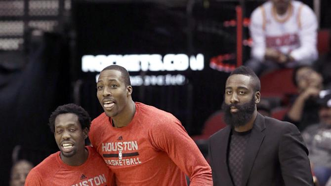 Houston Rockets Patrick Beverley, left, Dwight Howard, center, and James Harden watch as their teammates score a basket in the second half of an NBA basketball game against the Atlanta Hawks Wednesday, Nov. 27, 2013, in Houston. The Rockets won 113-84