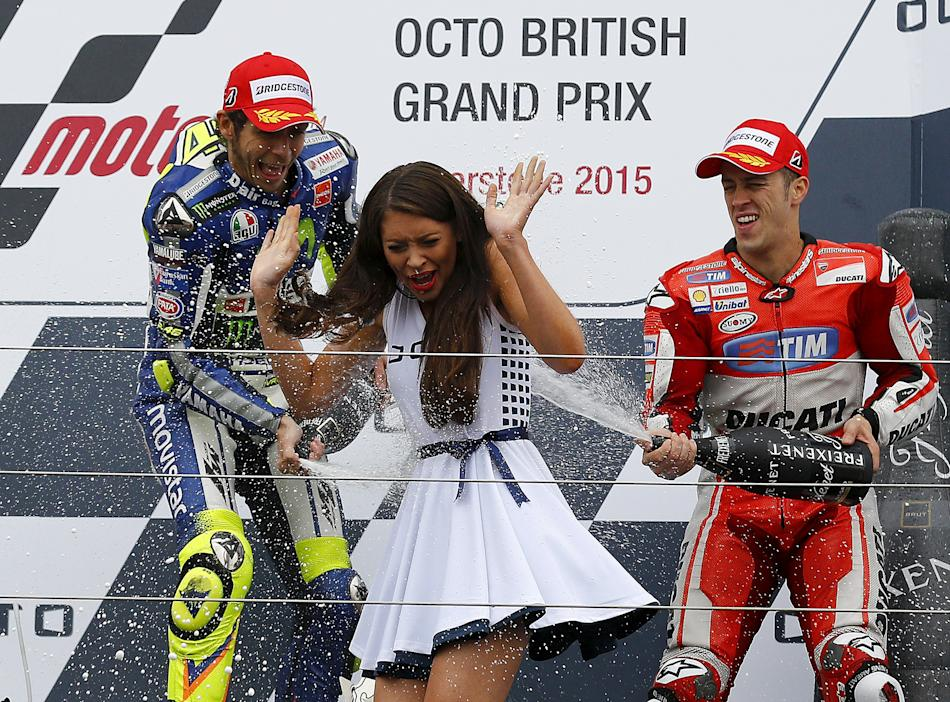 Winning Yamaha MotoGP rider Valentino Rossi of Italy and third placed Ducati MotoGP rider Andrea Dovizioso of Italy spray a grid girl after the British Grand Prix at the Silverstone Race Circuit