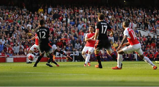 Arsenal's Mesut Ozil, centre, shoots and scores his sides second goal during the English Premier League soccer match between Arsenal and Manchester United at Emirates stadium in London, Sunday, Oc