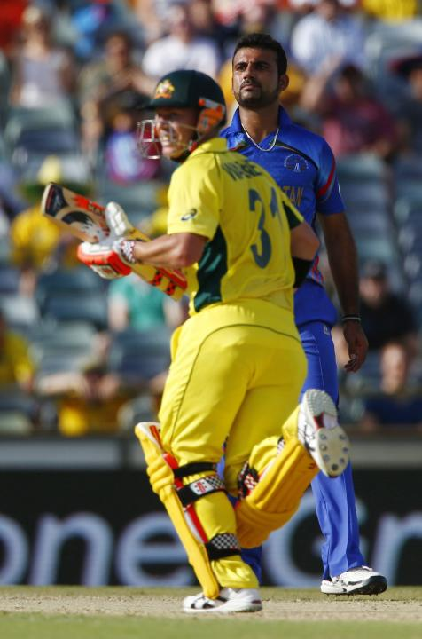 Afghanistan's bowler Dawlat Zadran watches as Australia's batsman David Warner hits another shot to the boundary during their Cricket World Cup match in Perth