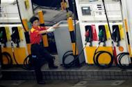 A petrol station worker motions toward an incoming car in Hong Kong in 2009. China, the world's second-biggest oil consumer, said it would cut fuel prices by more than three percent, following a retreat in global crude costs and amid concerns over inflation