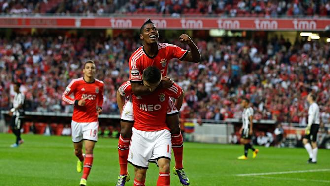 Benfica's Ivan Cavaleiro, top, jumps on the shoulders of teammate Siqueira celebrating after he scored the opening goal  during their Portuguese league soccer match with Nacional at Benfica's Luz stadium in Lisbon, Sunday, Oct. 27 2013