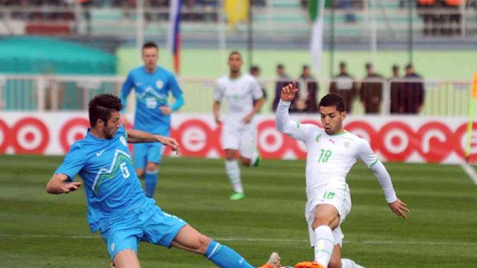 In this photo dated Wednesday, March 5, 2014, Algerian player, Abdelmoumene Djabou, right, vies for the ball with Bostjan Cesar of Slovenia during their friendly soccer match at Blida stadium, near the Algerian capital Algiers. Algeria defeated Slovenia 2-0