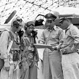 FILE - In this Sept. 16, 1950, file photo, Maj. Dean Hess, second from right, points out target area on map as he briefs two American-trained South Korean pilots just before takeoff as Brig. Gen. Kim Chung Yui, right, chief of staff of the Korean air force, looks on. Hess, a retired Air Force colonel who helped rescue hundreds of orphans in the Korean War and whose exploits prompted a Hollywood film, died Monday, March 2, 2015, at his home in suburban Dayton, Ohio, after a short illness. He was 97. (AP Photo/Jim Pringle, File)