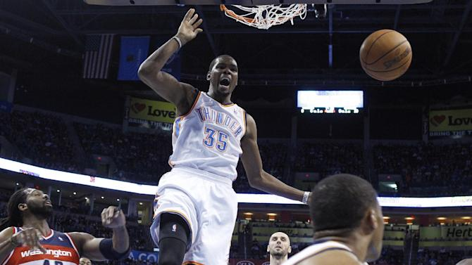 Oklahoma City Thunder forward Kevin Durant (35) reacts after dunking between Washington Wizards forward Nene (42) and center Marcin Gortat, right, in the first quarter of an NBA basketball game in Oklahoma City, Sunday, Nov. 10, 2013
