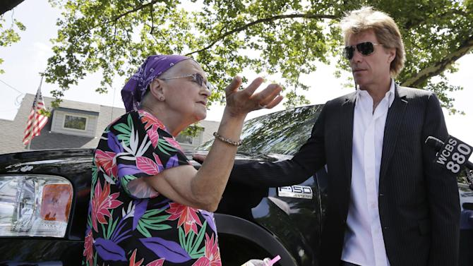 Sharon Mary Atkinson describes some of the devastation from Superstorm Sandy, as singer Jon Bon Jovi, right, listens Monday, July 8, 2013, as he walks in his hometown of Sayreville, N.J., with New Jersey Gov. Chris Christie. Bon Jovi is giving $1 million to help the band's home state recover from Superstorm Sandy. Bon Jovi has been a high-profile presence in his hometown since some neighborhoods were wiped out by Sandy last year. The singer says he wants to do what he can to help, including telling the world about the central New Jersey community's struggles. (AP Photo/Mel Evans, Pool)