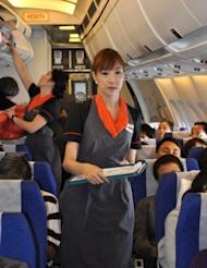 Transsexual fight attendant Chayathisa Nakmai (R), seen working onboard a Thai PC Air flight between Bangkok and Hong Kong. Fledgling Thailand-based carrier PC Air has hired four transgender cabin crew in a highly publicised recruitment drive that has divided opinion over whether the move is in the spirit of equality or exploitation