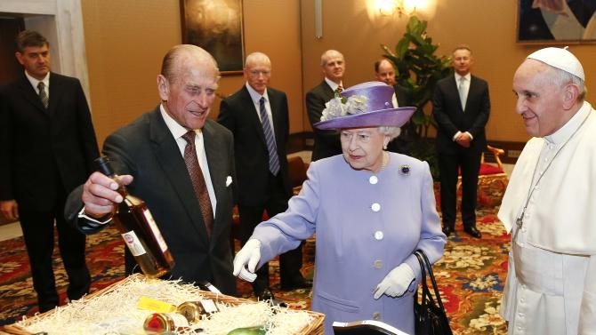 Britain's Queen Elizabeth and Prince Philip present gifts to Pope Francis during a meeting at the Vatican