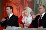 Russian President Vladimir Putin (R), Russian Prime Minister Dmitry Medvedev (L) and his wife Svetlana attend an Orthodox Easter celebration at the Cathedral of Christ the Savior in Moscow in the early hours of May 5, 2013. Thousands of Muscovites were due to rally Sunday in commemoration of a bloody protest one year ago