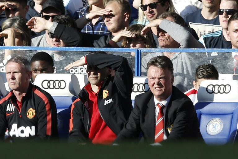 Manchester United's manager Louis van Gaal (R) and assistant manager Ryan Giggs (C) watch the action from the bench during the English Premier League football match in London on April 18, 2015