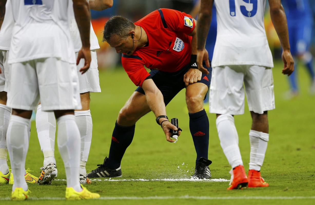 Referee Bjorn Kuipers of the Netherlands marks out a line with an invisible spray during the 2014 World Cup Group D soccer match between England and...