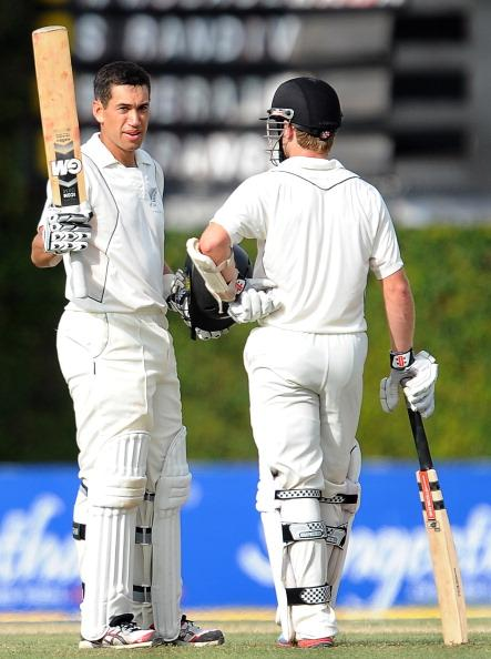 New Zealand captain Ross Taylor raises his bat and helmet in celebration after scoring a century (100 runs) as teammate Kane Williamson looks on during the first day of the second and final Test match
