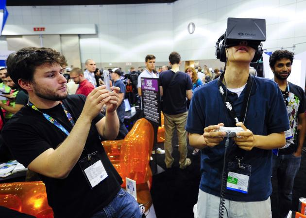 """Software designer Julian Kantor (L), who created """"The Recital"""", takes a picture of Jonathan Feng using the Oculus Rift virtual reality headset to experience his program during E3 in Los Angeles, California in this June 12, 2013 file photo. Facebook Inc will acquire two-year-old Oculus VR Inc, a maker of virtual-reality glasses for gaming, for $2 billion, buying its way into the fast-growing wearable devices arena with its first-ever hardware deal. On March 25, 2014, Facebook said virtual-reality technology could emerge as the next social and communications platform. REUTERS/Gus Ruelas/Files (UNITED STATES - Tags: SOCIETY BUSINESS SCIENCE TECHNOLOGY)"""
