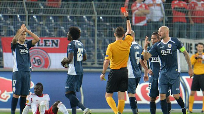 Referee Ivan Kruzliak shows the red card to Standard's Mehdi Carcela-Gonzalez, second from right,   during the Europa League group C soccer match  between Red  Bull Salzburg and Standard  Liege  in Salzburg, Austria, Thursday, Oct.  24, 2013
