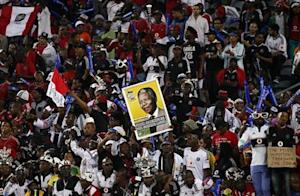 Fans of South Africa's Orlando Pirates hold a placard of anti-apartheid leader and former president Mandela during the first leg of their African Champions League final soccer match against Egypt's Al Ahli at Orlando Stadium in Soweto