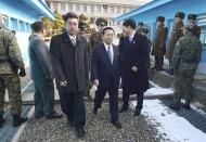 Head of the North Korean high-level delegation, Won Tong Yon (C) crosses the concrete border which separates the two Koreas at the truce village of Panmunjom in the demilitarised zone, north of Seoul February 12, 2014. North and South Korea held their first high-level talks in seven years on their armed border on Wednesday, exploring ways to improve ties while the South and the United States geared up for large-scale military drills that have angered Pyongyang. REUTERS/Unification Ministry/Yonhap (SOUTH KOREA - Tags: POLITICS) ATTENTION EDITORS - THIS IMAGE WAS PROVIDED BY A THIRD PARTY. FOR EDITORIAL USE ONLY. NOT FOR SALE FOR MARKETING OR ADVERTISING CAMPAIGNS. NO SALES. NO ARCHIVES. THIS PICTURE IS DISTRIBUTED EXACTLY AS RECEIVED BY REUTERS, AS A SERVICE TO CLIENTS. SOUTH KOREA OUT. NO COMMERCIAL OR EDITORIAL SALES IN SOUTH KOREA