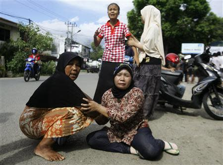 Women cry on a street in Banda Aceh after a strong earthquake struck off Indonesia