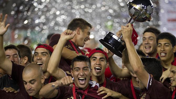 In this Wednesday, Dec. 11, 2013 photo, Argentina's Lanus celebrate after receiving the Copa Sudamericana trophy after defeating Brazil's Ponte Preta in the championship soccer final in Buenos Aires, Argentina. The Argentine club Lanus won its first international title by defeating Ponte Preta of Brazil 2-0