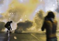 A protester reaches down to throw back a smoke canister as police clear a street after the passing of a midnight curfew meant to stem ongoing demonstrations in reaction to the shooting of Michael Brown in Ferguson, Missouri August 17, 2014. The group of protesters angry at the shooting death of Brown, a black teenager, by a white police officer remained on the streets of Ferguson, Missouri, early on Sunday minutes past the declared curfew, as police gathered nearby in a tense standoff. REUTERS/Lucas Jackson (UNITED STATES - Tags: CIVIL UNREST CRIME LAW)