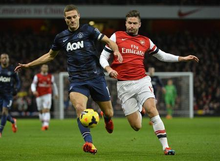 Arsenal's Giroud challenges Manchester United's Vidic during their English Premier League soccer match at the Emirates stadium in London