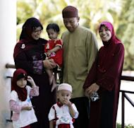 "In this picture taken Saturday, June 4, 2011, Malaysian Muslim Ishak Md Nor, second from right, 40, and his two wives, Aishah Abdul Ghafar, left, 40, and Afiratul Abidah Mohd Hanan, 25, who are members of the ""Obedient Wife Club,"" pose with their children after the club's launch in Kuala Lumpur, Malaysia. A Malaysian Muslim group has launched the ""Obedient Wives Club"" to teach women to be submissive and keep their spouses happy in the bedroom as a cure to social ills. (AP Photo)"