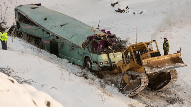 A piece of heavy equipment strains to move a bus which plummeted 200 feet down an embankment in rural Eastern Oregon Sunday, killing nine and sending multiple to hospitals, Monday, Dec. 31, 2012. Survivors of the bus crash said Monday some passengers were thrown from the tour bus through broken windows after the vehicle skidded out of control, smashed through a guardrail and went down. (AP Photo/The Oregonian, Randy L. Rasmussen)