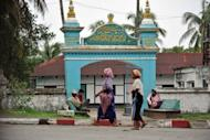 Muslim women walk past a mosque in Sittwe, capital of Myanmar's western Rakhine state. Myanmar's reformist government has launched an official probe into a flare-up of sectarian violence in the west of the country, state media said, pledging to punish those responsible