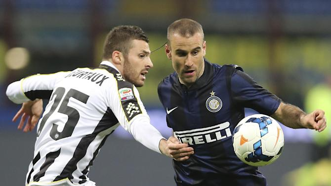 Inter Milan forward Rodrigo Palacio, right, of Argentina, challenges for the ball with Udinese defender Thomas Heurtaux, of France, during a Serie A soccer match between Inter Milan and Udinese at the San Siro stadium in Milan, Italy, Thursday, March 27, 2014