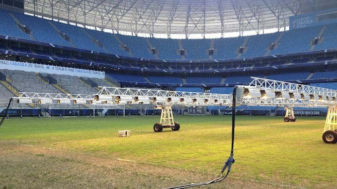 In this photo taken on Dec. 15, 2013, giant lighting rigs pictured,  helping to grow the reseeded pitch, at the new Gremio Arena, in the southern Brazilian city of Porto Alegre, which will be a training venue during the World Cup.  At Arsenal's Highbury Stadium, Edu played on one of football's finest pitches. Award-winning Arsenal groundsman Paul Burgess became so well-known for his green fingers that he was eventually lured away by Real Madrid. So when Edu returned home to Brazil in 2009 to finish his career, the worn and sorry state of some Brazilian football fields was an eye-opener. Even now, as the World Cup host rushes to ready itself, Edu says pitches in Brazil aren't on a par with those in Europe, where he played for eight years, at Arsenal and Valencia