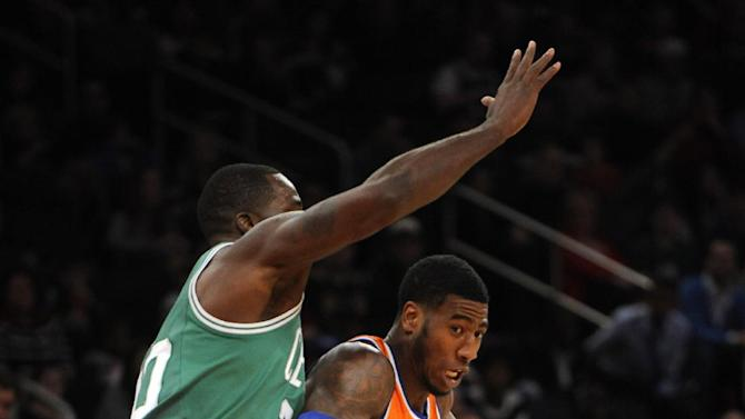 New York Knicks' Iman Shumpert, right, tries to drive the ball around Boston Celtics' Brandon Bass, left, during the first half of an NBA basketball game on Sunday, Dec. 8, 2013, in New York. The Celtics won 114-73