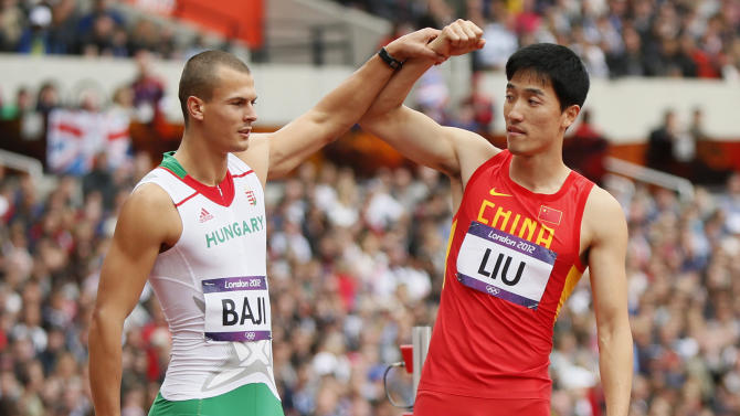 China's Liu Xiang has his arm held up by Hungary's Balazs Baji after crashing into the first hurdle during their men's 110m hurdles round 1 heat at the London 2012 Olympic Games