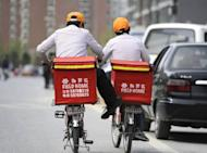 Two workers deliver fast food in Beijing on April 12, 2012. China said Friday its economy grew by 8.1 percent in the first three months of 2012, its slowest pace in nearly three years, as global turbulence curbed business activity