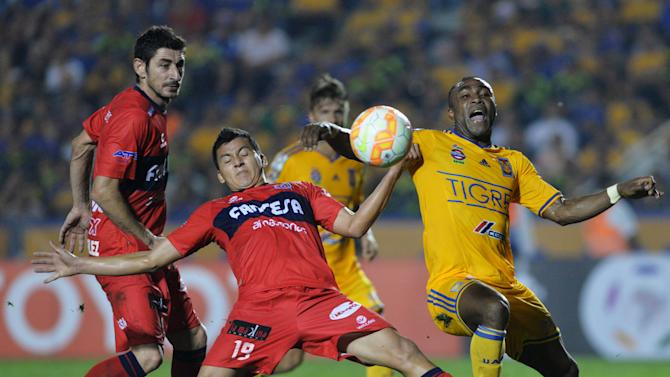 Jorge Enrique Flores of Bolivia's Universitario de Sucre battles for the ball with Joffre David Guerron of Mexico's Tigres during their Copa Libertadores soccer match