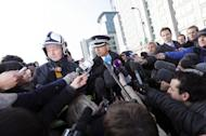Commander Neil Basu (centre) and London Fire Brigade assistant commissioner Peter Kowup (left) speak to journalists near the scene of a helicopter crash in central London on January 16, 2013. Two people were killed on Wednesday when a helicopter hit a crane at a building site in central London during morning rush hour and plunged to the ground in a ball of flames
