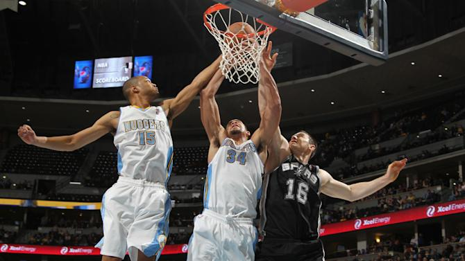 Denver Nuggets forward JaVale McGee, center, pulls down a rebound as teammate Anthony Randolph, left, San Antonio Spurs center Aron Baynes reach for the ball in the third quarter of the Nuggets' 98-94 victory in an NBA preseason basketball game in Denver on Monday, Oct. 14, 2013