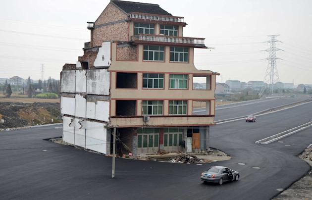 An elderly couple in Wenling, Zhejiang province, refused to move when local government officials planned to build a highway that would run through their village. The homeowner, Luo Baogen rejected the