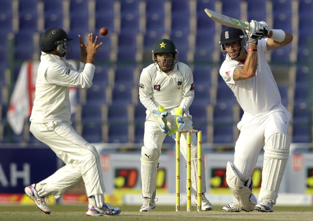 England's Kevin Pietersen, right, hits the ball watched by Pakistan's Adnan Akmal, center, as his teammate Azhar Ali tries to catches the ball during the second day of the second cricket test match of