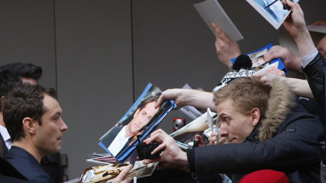 Actor Jude Law signs autographs as he arrives for the photo call of the film Side Effects at the 63rd edition of the Berlinale, International Film Festival in Berlin, Tuesday, Feb. 12, 2013. (AP Photo/Michael Sohn)